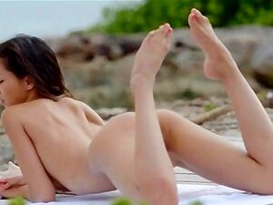 Asian angel undressing by the ocean
